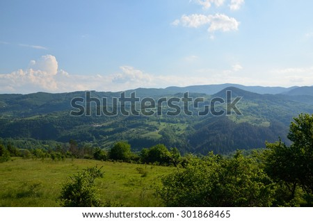 Meadow, hills, valleys and mountains with lush trees - stock photo