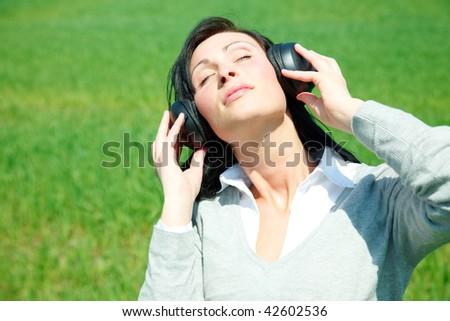 Meadow listening music girl with headphones - stock photo