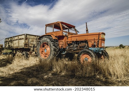 meadow, old agricultural tractor abandoned in a farm field - stock photo