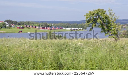 Meadow, river and a camping in bright sunshine in the Nordic countryside. - stock photo