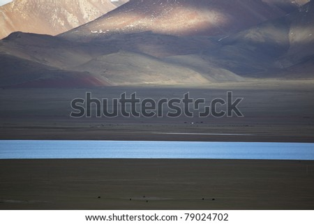 meadow with a river on the altiplano in the northwest of china - stock photo