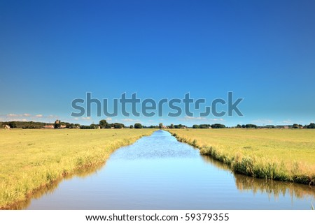 Meadow with canal under blue sky - stock photo