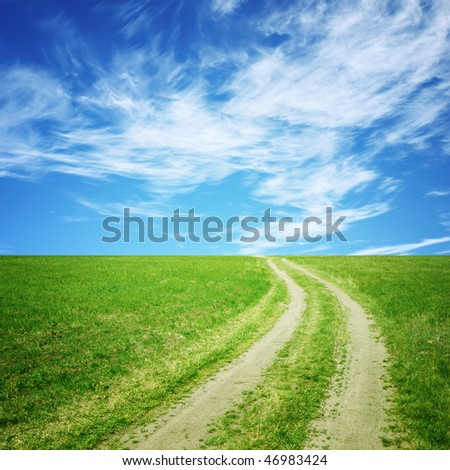 Meadow with dirt road and blue sky. Summer landscape - stock photo