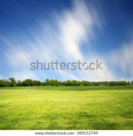 Meadow with green spring grass. Clouds in blurred motion due to long exposure above the row of trees - stock photo