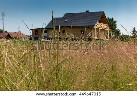 meadow with tall grass around a wooden house - stock photo