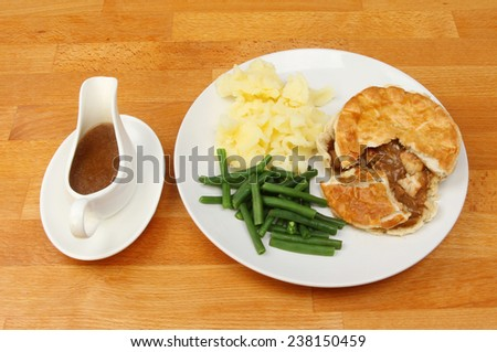 Meal on a tabletop, chicken pie potatoes and beans with gravy in a gravy boat - stock photo