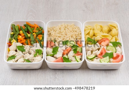 Meals of chicken with different side dish in plastic containers on wooden table
