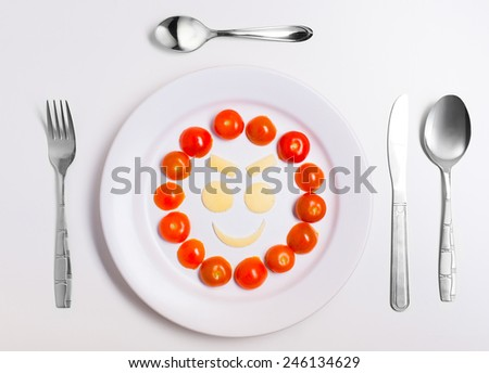 mean emoticon food, made from cheese and tomatoes, on a plate with cutlery, isolated