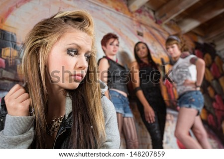 Mean group of people looking over at insecure teen - stock photo