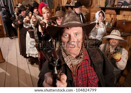 Mean gunfighter with pistol aimed in old saloon - stock photo