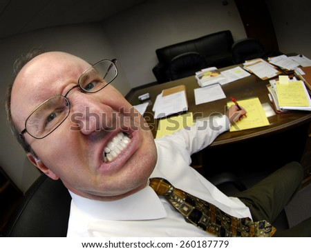 Mean looking man in business office gritting teeth - stock photo