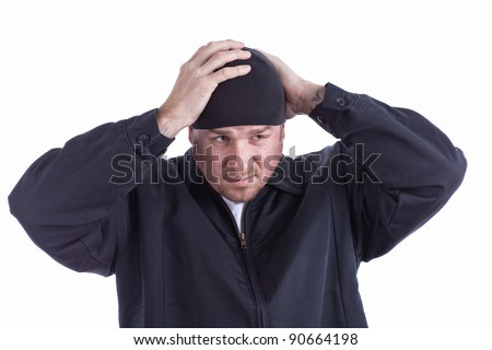 Mean Looking Man Putting On A Beanie Hat - stock photo