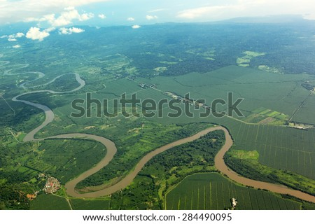 Meandering river viewed from the airplane - stock photo