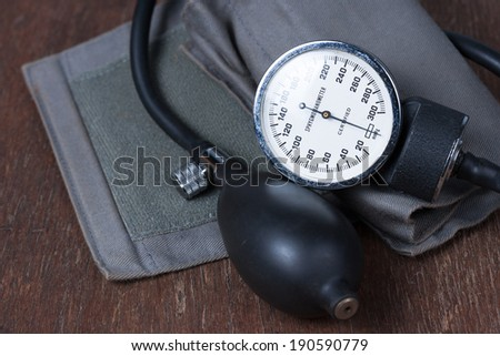 Measure blood pressure on wood table - stock photo
