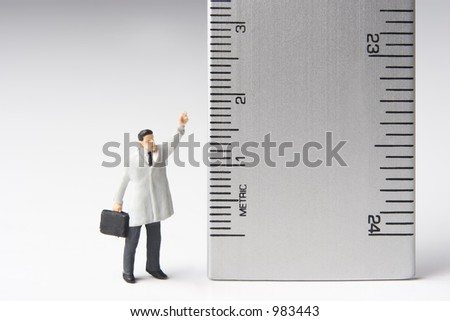 Measure of a man, business figure standing next to a ruler - stock photo