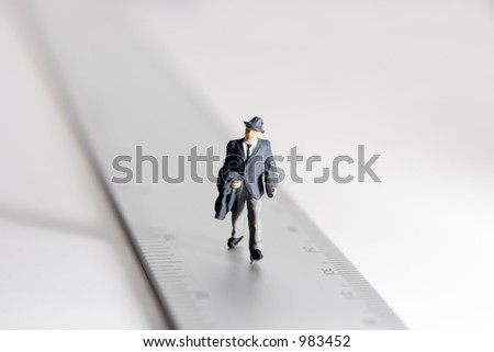 Measure of a man, business figure standing on a ruler - stock photo