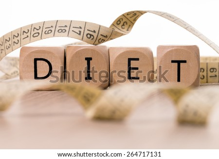 Measure tape and wood dice with the word Diet / Diet - stock photo