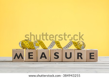 Measure tape on a wooden sign on a table - stock photo