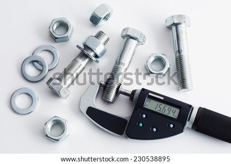 Measurement of details in the bolts and nuts industry. Measuring a diameter of a bolt with digital micrometer - stock photo