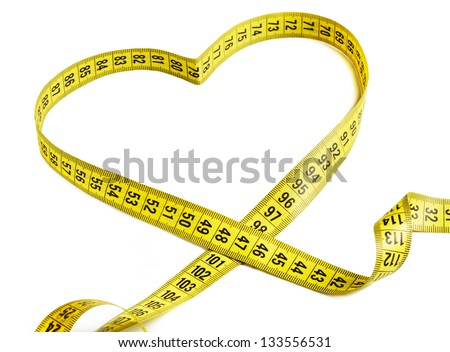 Measurement tape forming the shape of a heart - stock photo