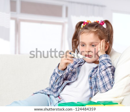 measures the temperature of a sick little girl lying on the couch - stock photo
