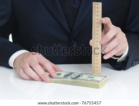 measuring a pile of dollars - stock photo