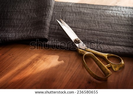 Measuring and cutting textile or fine cloth. Work table of a tailor. Gold scissors and black silky fabric.  - stock photo