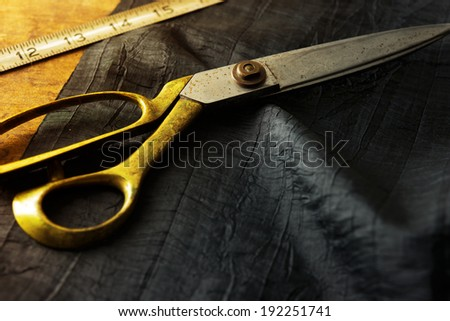 Measuring and cutting textile or fine fabric. Work table of a tailor. Gold scissors and black fabric.  - stock photo