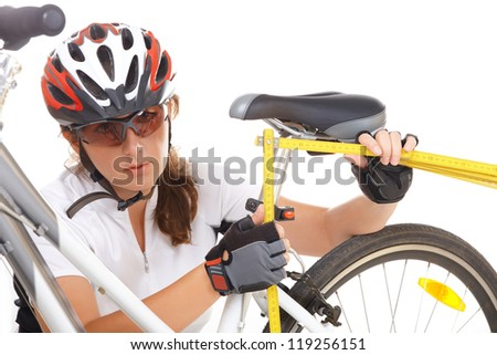 Measuring and making an adjustment in the bike saddle - stock photo