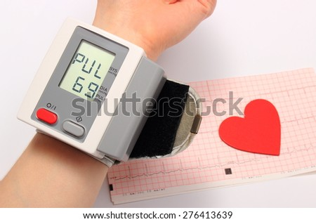 Measuring blood pressure and heart shape on electrocardiogram, medicine concept - stock photo