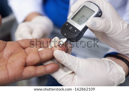 Measuring blood sugar with a blood glucose meter - stock photo