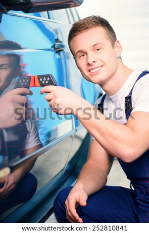 Measuring coating thickness. Closeup of a handsome car mechanic checking the thickness of car coating with a special electronic tool in car repair station - stock photo