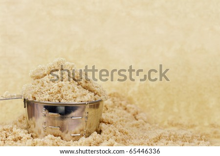 Measuring cup overflowing with sweet brown sugar. Room for copy space. - stock photo