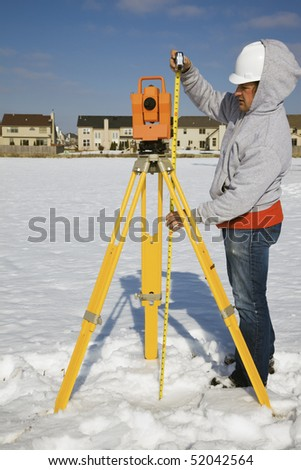 Measuring height of theodolite - winter time surveying. - stock photo