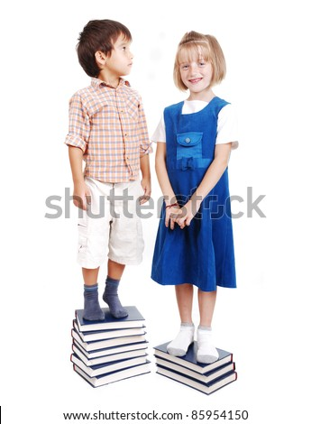 Measuring length on books, growing up, boy and girl - stock photo