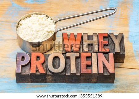 measuring metal scoop of whey protein powder against wood background with a text in vintage letterpress wood type - stock photo