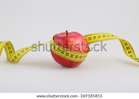 Measuring metre round a red apple on a white background close up