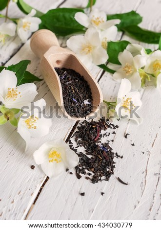 Measuring scoop with black tea and fresh jasmine flowers - stock photo