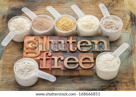 measuring scoops of gluten free flours (almond, coconut, teff, flaxseed meal, whole rice, brown rice, buckwheat) wit a text in letterpress wood type - stock photo