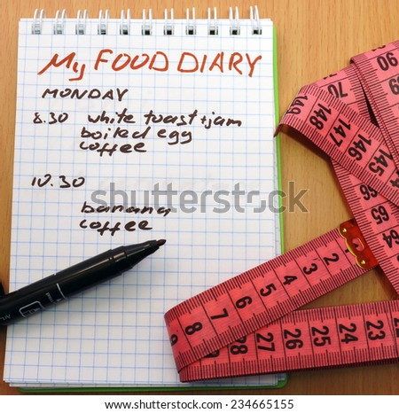 Measuring tape, a marker and a notepad with a food diary - stock photo