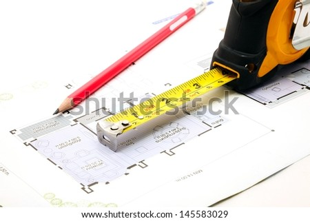 measuring tape and a pencil over a construction blueprint of a house - stock photo