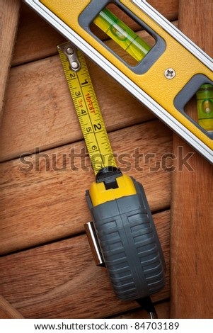 Measuring tape and bubble level on a wooden boards background - stock photo