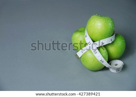 Measuring tape and green apple. Tools for the sport. The concept - stock photo