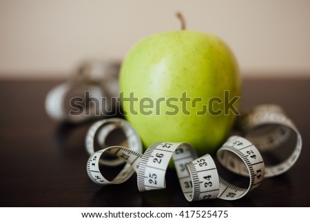 Measuring tape and green apple. Tools for the sport. The concept of a healthy lifestyle. - stock photo