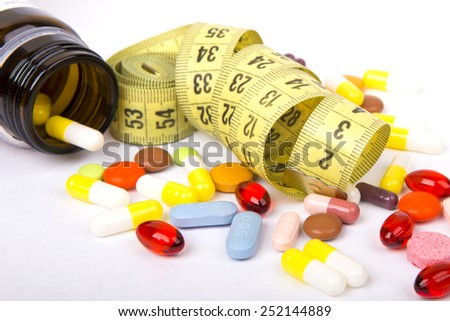 Measuring tape and pills for dieting concept - stock photo