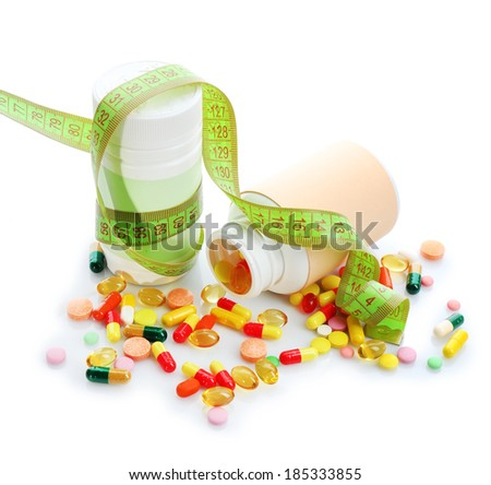 Measuring tape and pills, isolated on white. Dieting concept - stock photo