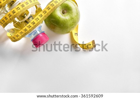 Measuring tape around a bottle of mineral water and apple on white table. Concept health, diet and nutrition. Horizontal composition. Top view - stock photo