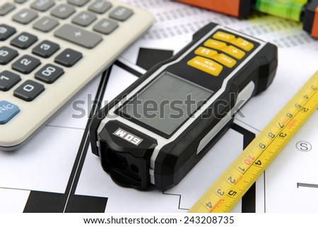 measuring tape, calculator, laser rangefinder and water level on plans  - stock photo