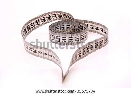 Measuring tape looking as heart - stock photo