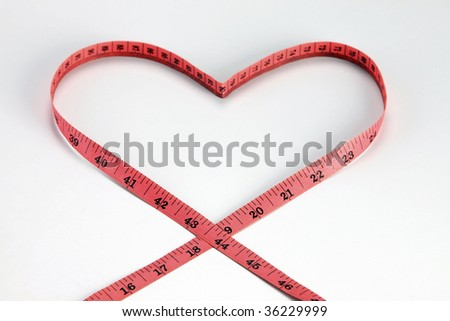 Measuring tape makes heart on the plain background - stock photo